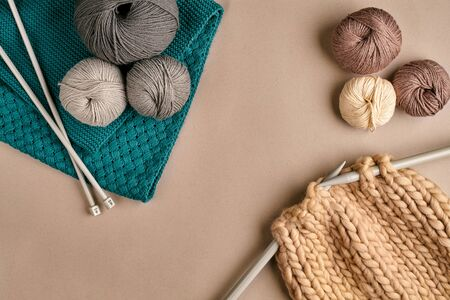 Grey and brown ball wool and knitting on needles on beige background. Knitting as a kind of needlework. Colorful balls of yarn and knitting needles. Top view. Still life. Copy space. Flat lay