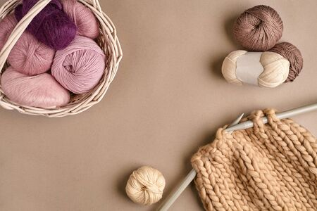 Pink and brown ball wool and knitting on needles on beige background. Knitting as a kind of needlework. Colorful balls of yarn and knitting needles. Top view. Still life. Copy space. Flat lay