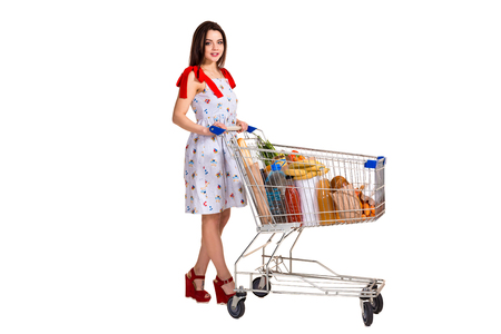 Young woman with full shopping cart on white background