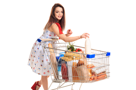 Smiling young woman doing grocery shopping at the supermarket, she is putting a milk bottle in the cart