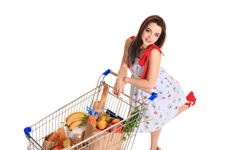 High angle view of girl smiling at camera while pushing a shopping cart full with groceries isolated on white background.
