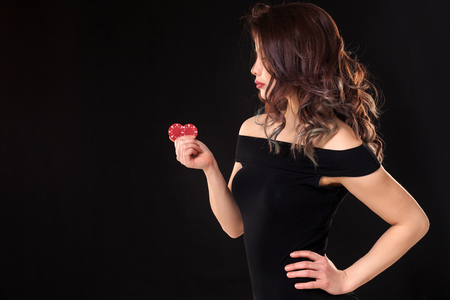 Smiling girl holding a gambling chips in her hands on black background. Copy space Stock Photo - 97209108