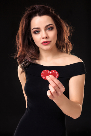 Smiling girl holding a gambling chips in her hands on black background. Stock Photo