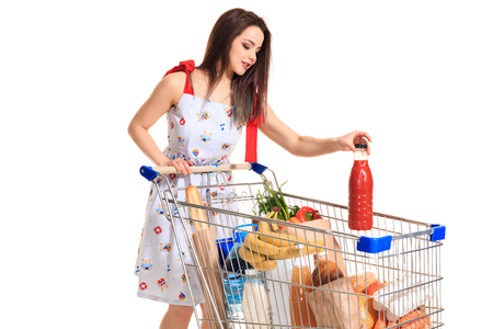Smiling young woman doing grocery shopping at the supermarket, she is putting a tomato juice bottle in the cart