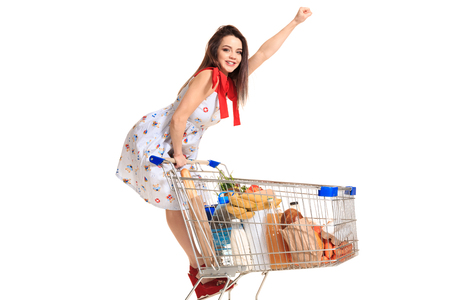 Woman with shopping cart full with products isolated over white background