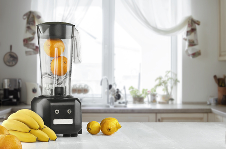 Metal food blender close-up with fresh exotic tropic fruits next to it on kitchen background with empty space