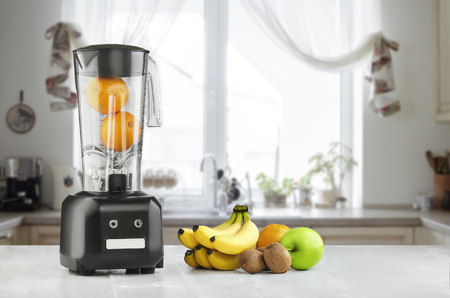 Blender, fruits and kitchen space Imagens