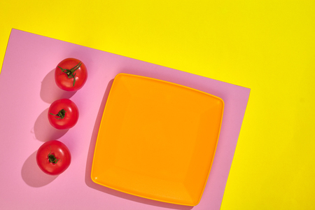 Empty orange plate on a yellow and pink table with red ripe cherry tomatoes, top view with copy space