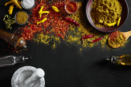 Cooking using fresh ground spices with mortar and small bowls of spice on a black table with powder spillage on its surface, overhead view with copyspace