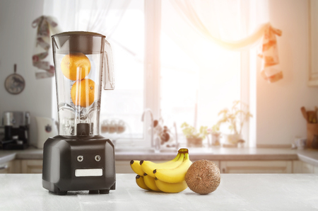 Metal food blender close-up with fresh exotic tropic fruits next to it on kitchen background with empty space. Sun flare