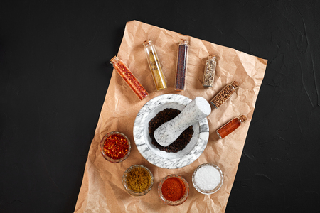 Various oriental spices and white marble mortar on black background with copy space. Still life. Flat lay. Top view. Stock Photo