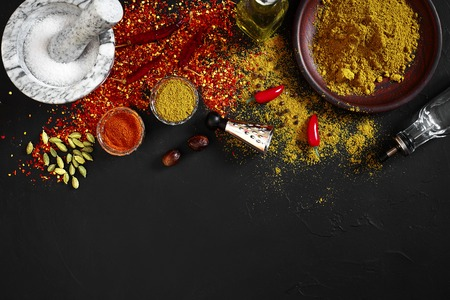 Cooking using fresh ground spices with mortar and small bowls of spice on a black table with powder spillage on its surface, overhead view with copyspace. Still life. Flat lay. Top view. Banco de Imagens