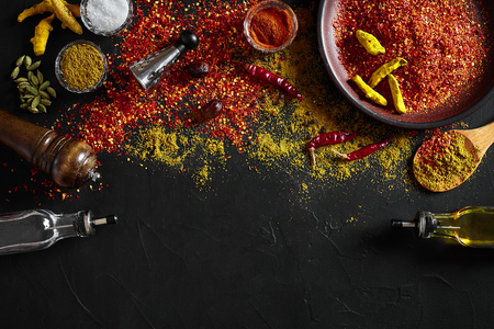 Cooking using fresh ground spices with big and small bowls of spice on a black table with powder spillage on its surface, overhead view with copyspace. Still life. Flat lay. Top view.
