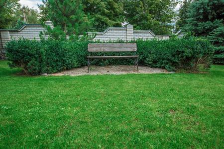 Wooden bench in a beautiful park garden. Summer Stock Photo