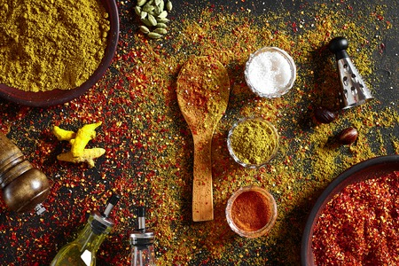 Assorted spices on dark black background. Seasonings for food. Curry, paprika, pepper, cardamom, turmeric. Top view. Close-up. Spices concept. Spices ingredients for cooking Stock Photo