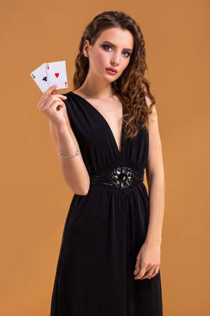 Young woman holding playing cards against a orange background. Studio shot Stock Photo