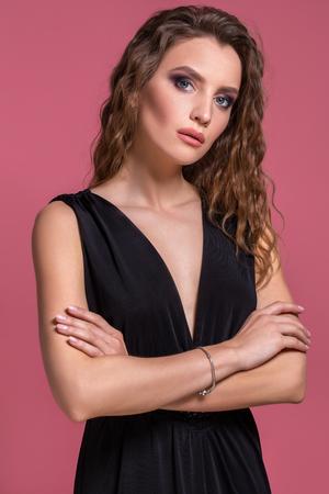 Portrait of beautiful young woman in black dress. Fashion photo