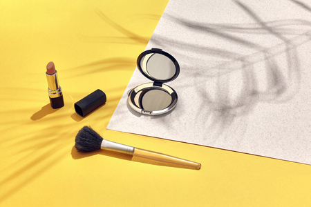 Woman's accessories lying flat on paper background. Yellow and white pastel colors with copy space around products. Horizontal image or photograph. Still life