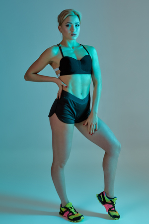 Fitness woman in black tank top and shorts, studio shot.