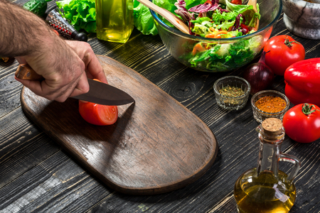 Mans hand cuts ripe red tomatoes for summer healthy vegetable salad on a wooden board, vertical Stock Photo