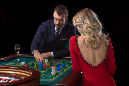 A beautiful young woman and a man are sitting at a roulette table. Casino.