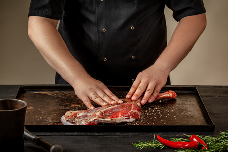 Male chef rubbing raw lamb shanks with salt and pepper on stone tray on wooden table. Chef cooking appetizing shank of lamb.