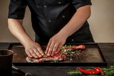 Male chef rubbing raw lamb shanks with greens and spices on stone tray on wooden table. Chef cooking appetizing shank of lamb.