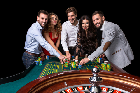 Group of young people behind roulette table in a casino