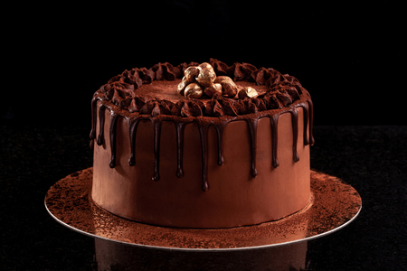 Chocolate cake with nuts on a black background 스톡 콘텐츠
