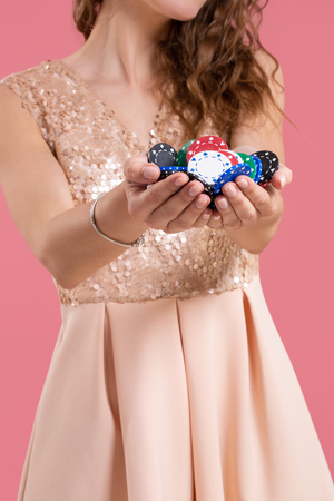 Woman holding a gambling chips in her nands on pink background. Close-up