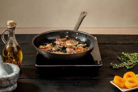 Roasted quail in a frying pan on wooden background