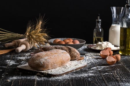 Beautiful still life with different kinds of bread, grain, flour on weight, ears of wheat, pitcher of milk and eggs Stock Photo