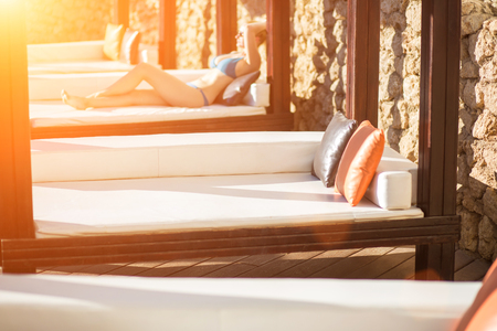 Young woman relaxing on the deck chair by the swimming pool at the resort. Sun flare Stock Photo