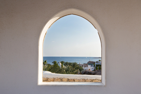 Egypt. A look through the frame on the palm trees. Beautiful view. White house and veranda overlooking the sea and palm trees. Stock Photo