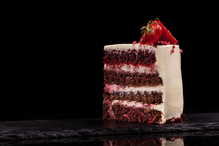 Piece of strawberry cake on a black background. Stock Photo