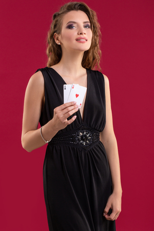 Beautiful young woman with a playing cards on red background