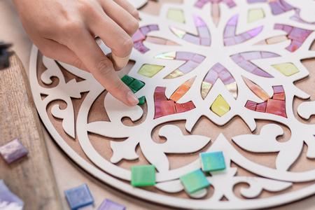 Luogo di lavoro del maestro del mosaico: le mani delle donne tengono uno strumento per i dettagli del mosaico nel processo di realizzazione di un mosaico