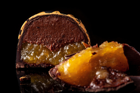 Cut luxury handmade candy with chocolate and yellow confiture filling on black background.