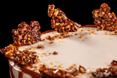 Round white cake with caramel and chocolate puffed rice on a round tray on black background