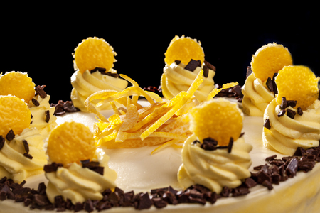 Round yellow birthday cake. Decorative cream decorations on the cake. Black background. Close-up