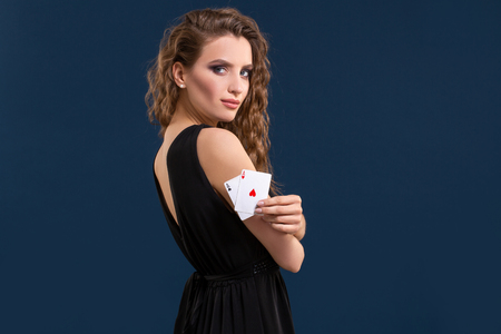Beautiful brunette holding two aces as a sign for poker game, gambling and casino