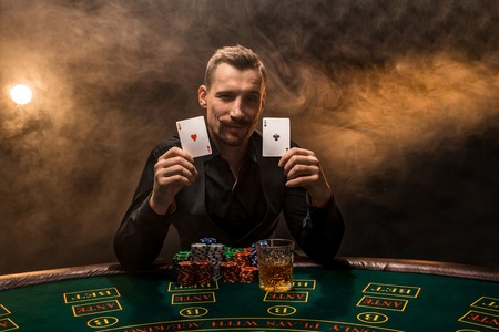 Bearded man showing poker cards on smoke black background