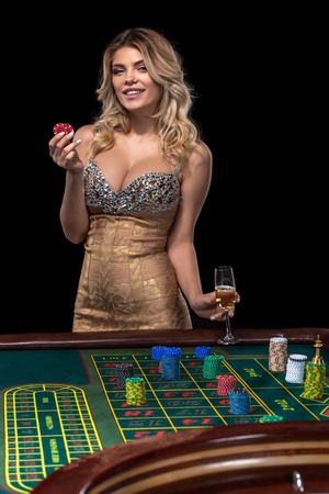 Young blonde woman wearing beautiful sexy shiny dress is playing roulette in the casino Stock Photo