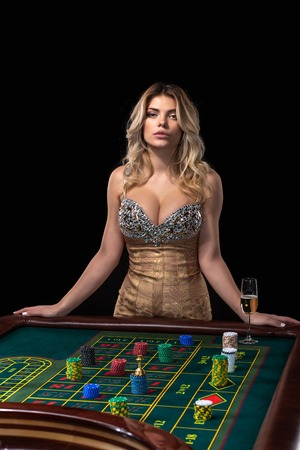 Young blonde woman wearing beautiful sexy shiny dress is playing roulette in the casino Standard-Bild