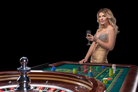 Young blonde woman wearing beautiful shiny dress is playing roulette in the casino