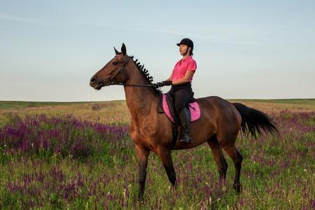 Horsewoman jockey in uniform riding horse outdoors
