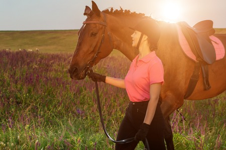 Beautiful young girl smile at her horse dressing uniform competition: outdoors portrait on sunset. Sun flare Stock Photo
