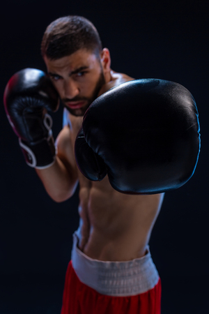 Portrait of tough male boxer posing in boxing stance against black background.
