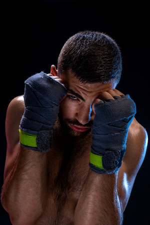 Determined young man with athletic body wearing training bandages posing in defensive position, holding pumped fists in front of his face and staring at camera on black background.