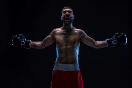 Oriental boxer celebrating his victory with raised arms in black gloves on black background